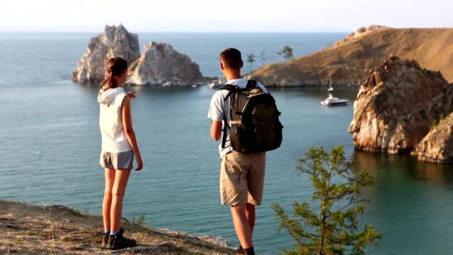 Couple walking at the coast of beautiful lake video