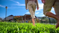 Couple walking barefoot on a grass towards the park video