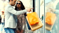 Couple walking by retail stores. video