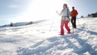 Couple walking downhill with snowshoes video