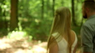 CLOSE UP DOLLY SHOT  Couple walking in forest on sunny day video