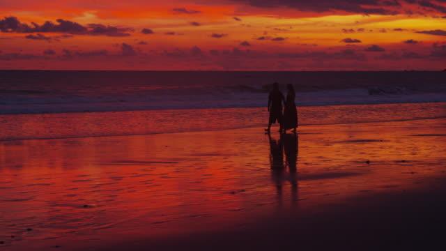 Couple walking on beach at sunset video