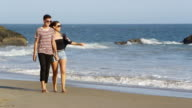 Couple walking on beach together video