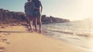 Couple walking on the beach. video