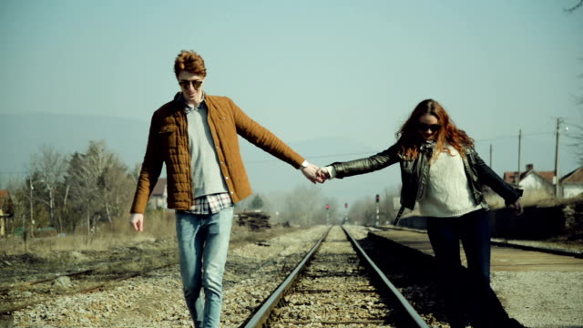 Couple walking on the rail tracks video