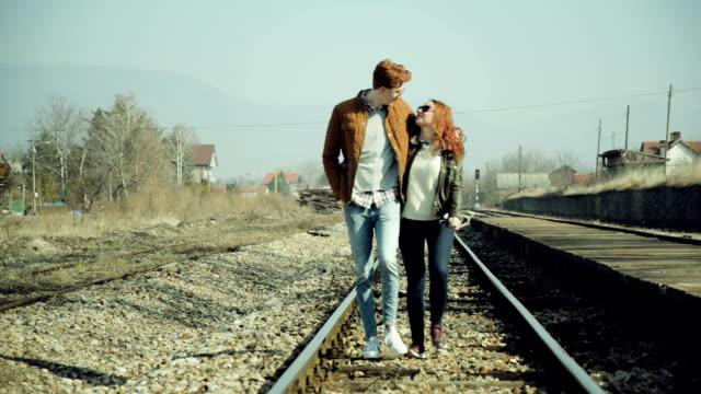 Couple walking on the rail tracks video