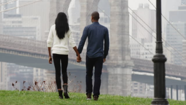 A couple walks hand in hand through the Brooklyn Bridge park after a rain video