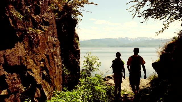 Couple walks on rocky coast of big lake video