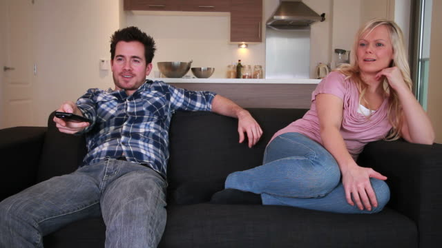 Couple watching television on sofa video