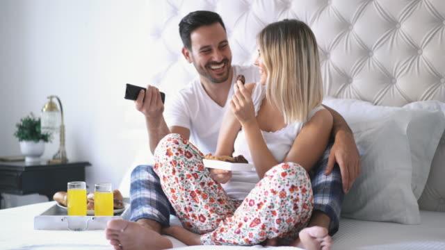 Couple watching tv in bedroom. video