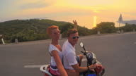 POV Couple waving while riding a scooter video