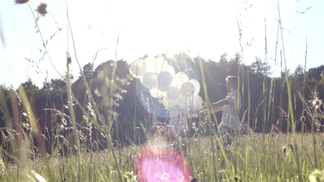 Couple whirl with balloons in the field video