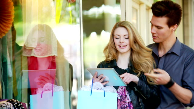 Couple window shopping with a tablet video