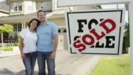 Couple with 'For Sale, Sold' real estate sign video