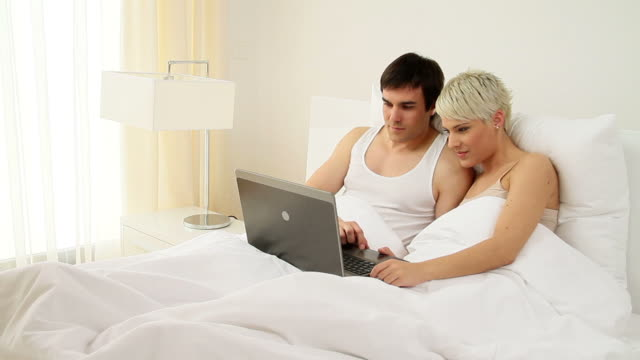 Couple with laptop in bed video
