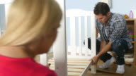 Couple With Pregnant Wife Assembling Cot In Nursery video