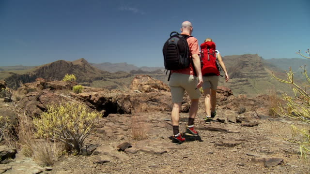 couple with rucksacks hiking in volcanic landscape video