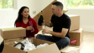 Couple with unpacked boxes toasting video