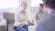 Couple working on their finances at home with a financial planner video