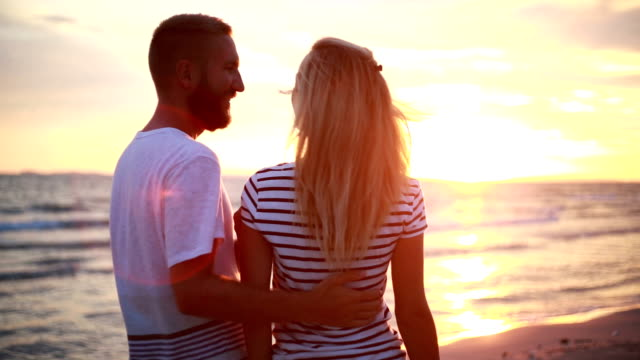 Couples hugging by the beach at sunset video