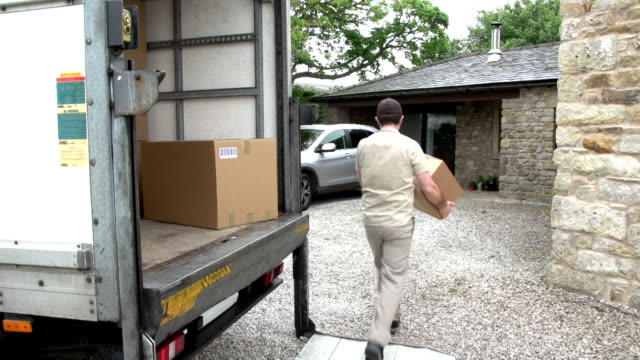 Courier / Delivery man delivering a Package to a home video