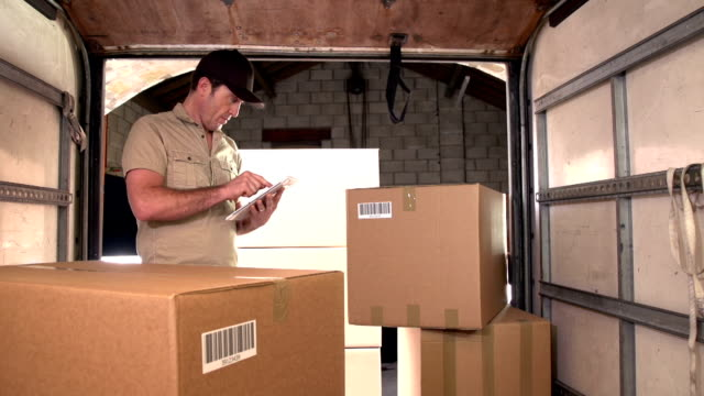 Courier / Delivery man on Digital Tablet in Delivery Truck video