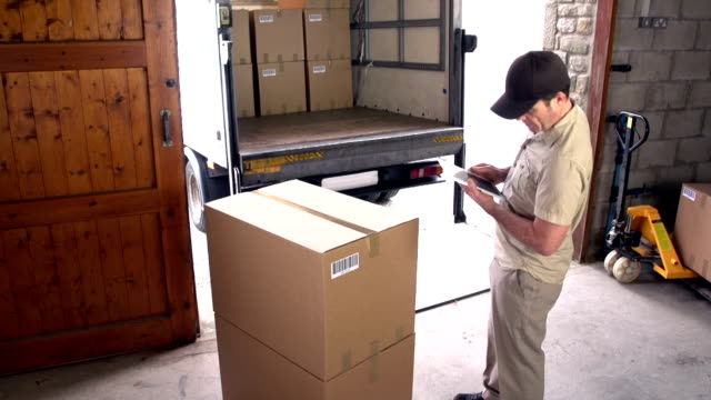 Courier / Delivery man on Digital Tablet in Warehouse video