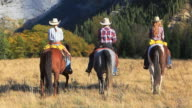 Cowboy and two cowgirls riding towards the mountains video