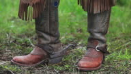 Cowboy boots, spurs, chaps and horse eating video