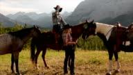 Cowboy/ cowgirl exchange kisses on horseback video