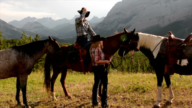 Cowboy/ cowgirl exchange kisses on horseback video