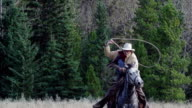 Cowboy galloping on horseback Swinging lariat video