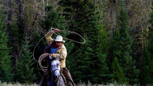 Cowboy galloping on horseback Swinging lariat video