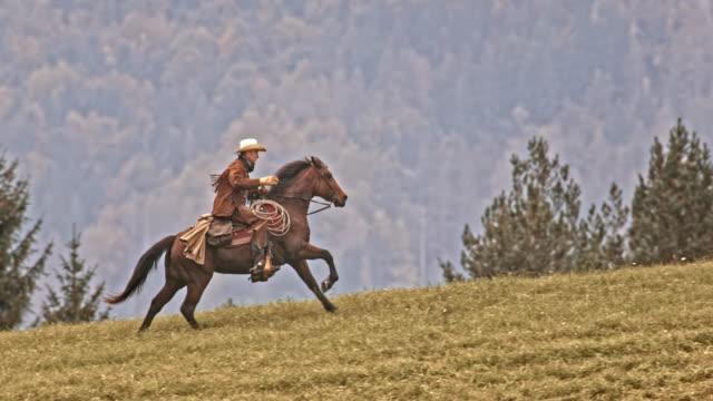 SLO MO TS Cowboy riding his galloping horse uphill video