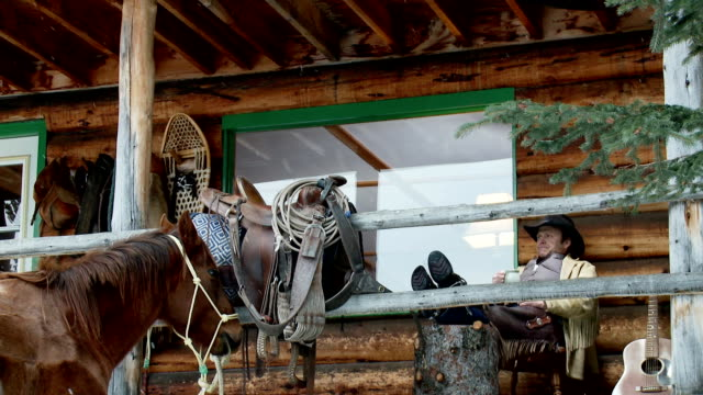 Cowboy sits on porch outside log cabin video