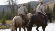Cowboys and Cowgirl crossing river on horseback video
