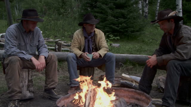 Cowboys sit around a fire at dusk video