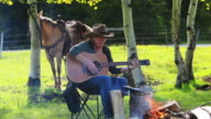 Cowgirl playing Guitar around campfire with horse video