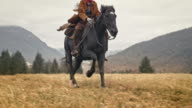 SLO MO Cowgirl riding a galloping horse across meadow video