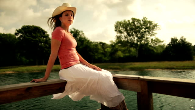 Cowgirl Sitting on the Railing of a Pier video