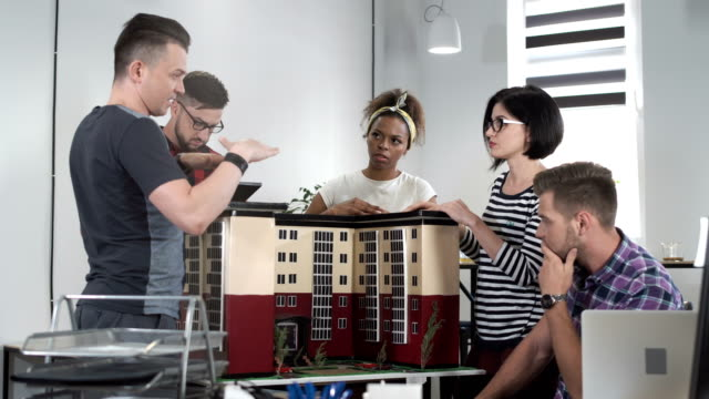 Co-workers discussing by miniature of building video