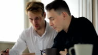 Co-working men are discussing business project in office video