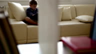 Cozy home scene: a boy sits on a couch and reads a book video