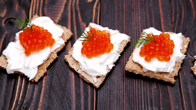 crackers with cream cheese and red caviar close-up video