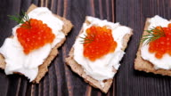 crackers with cream cheese and red caviar close-up - Vidéo