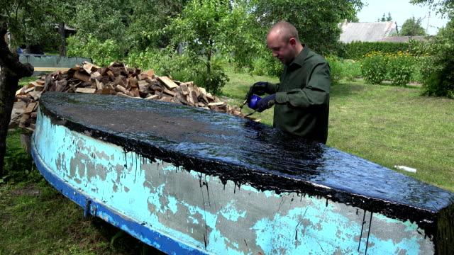 Craftsman man with gas burner and tar repair his boat. FullHD video