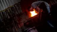 Craftsperson working furnace in blacksmith's shop shoveling coal video