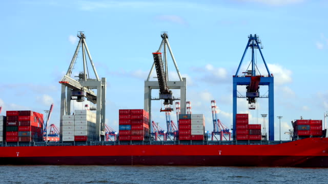 cranes loading a container ship at harbour video