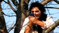 Crazy Dark-Haired Woman In Long White Nightie Putting On Lipstick Sitting On Tree video