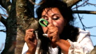 Crazy Dark-Haired Woman In Long White Nightie Putting On Mascara Sitting On Tree video